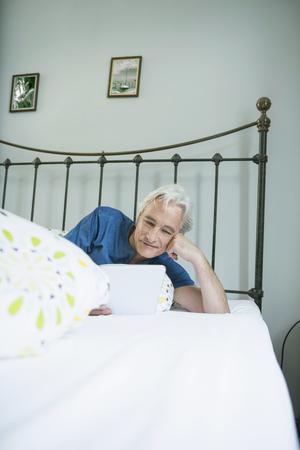 time sensitive: Mature man using digital tablet in bed, smiling
