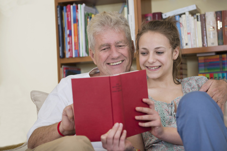 60 65 years: Grandfather and granddaughter reading book on couch in living room, smiling LANG_EVOIMAGES