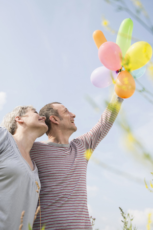 looking for love: Mature couple with bunch of balloons, smiling LANG_EVOIMAGES