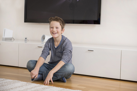 sitting on the ground: Smiling boy sitting on floor in living room LANG_EVOIMAGES