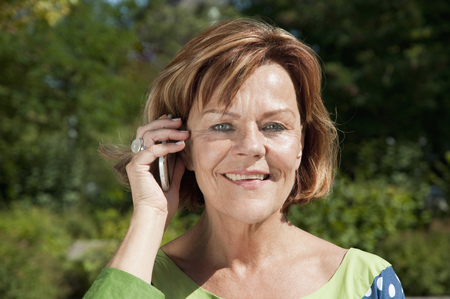 Senior woman talking on smart phone, smiling, portrait LANG_EVOIMAGES