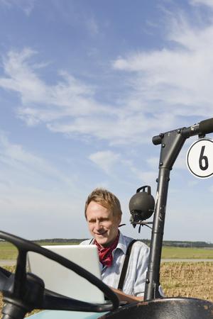 non urban 1: Mature man with laptop on cornfield, Bavaria, Germany