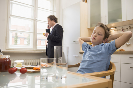 overstress: Bored boy in kitchen with father on the phone in background