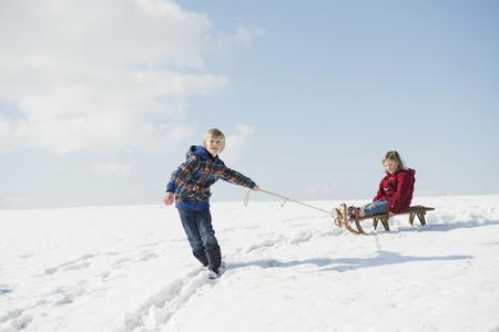 Boy pulling girl on sledge, Bavaria, Germany