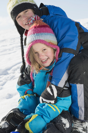 anorak: Portrait of brother and sister sledging, smiling, Bavaria, Germany LANG_EVOIMAGES