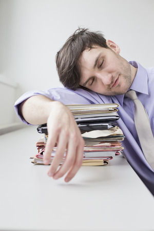 overstress: Businessman sleeping on stack of files in office LANG_EVOIMAGES