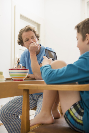 morose: Father looking at son playing video game at breakfast table LANG_EVOIMAGES