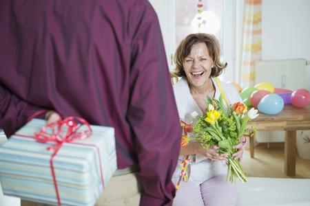 Senior man hand over present to woman on birthday, smiling