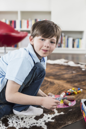 Portrait of boy playing with board game, smiling