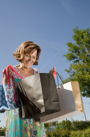 60 65 years: Senior woman looking into shopping bag
