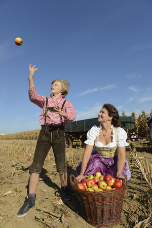 cowering: Mother and son playing with apples in field, Bavaria, Germany LANG_EVOIMAGES