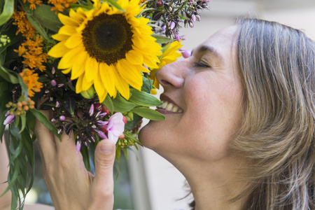 Mid adult woman with bouquet, smiling LANG_EVOIMAGES