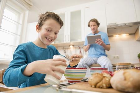 niños desayunando: Padre con tableta digital y cocina hijo LANG_EVOIMAGES