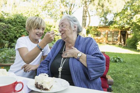 10 11 years: Grandson feeding his grandmother with cream cake