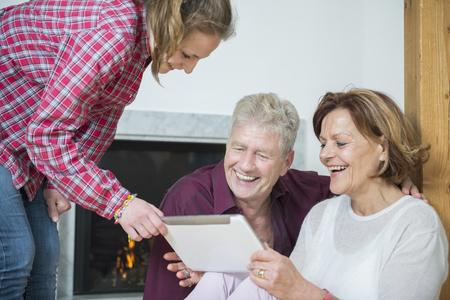 time sensitive: Granddaughter showing something on digital tablet to her grandparents, smiling