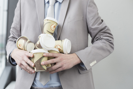 Businessman holding coffee cups to go for all, close up