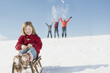 Portrait of girl sitting on sledge, family playing in background, Bavaria, Germany