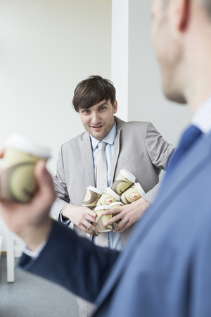 Businessmen holding coffee cups to go for all LANG_EVOIMAGES