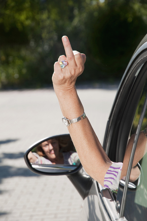 irrespeto: Senior woman sitting in car and making rude sign LANG_EVOIMAGES