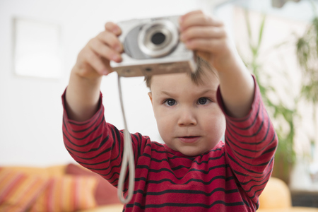 Boy taking pictures with camera LANG_EVOIMAGES