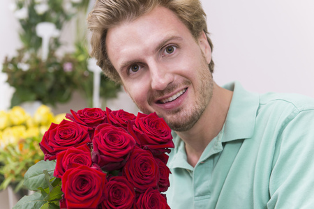 cowering: Portrait of mid adult man holding flowers, smiling