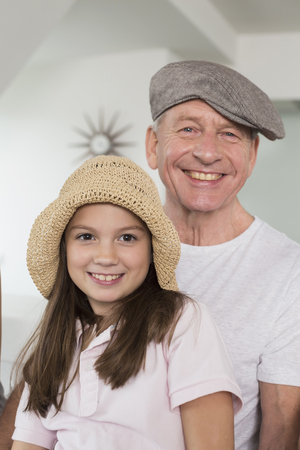 Smiling grandfather and granddaughter wearing hats, portrait