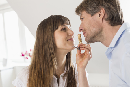 Couple smelling wine cork, smiling