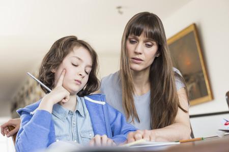 Mother helping daughter in homework LANG_EVOIMAGES