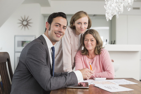 figuring: Smiling consultant and mature and young woman at home