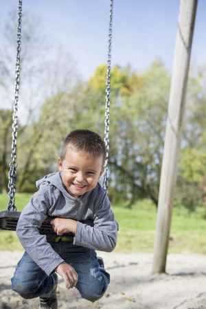 luft: Young small boy hanging playground swing