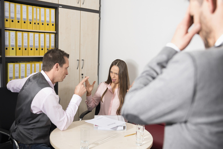 hassle: Young couple arguing office aggression mobbing