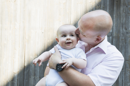 lust for life: Father kissing holding baby son proud smiling LANG_EVOIMAGES