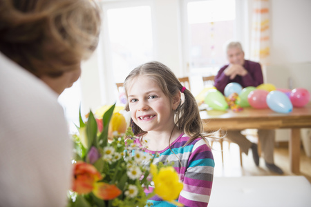 likeable: Granddaughter hand over bunch of flowers to her grandmother while grandfather in background