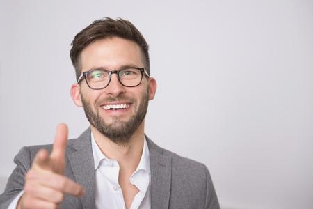 premises: Young businessman smiling pointing portrait LANG_EVOIMAGES