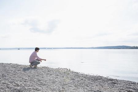 skimming: Man alone lake skimming stones LANG_EVOIMAGES