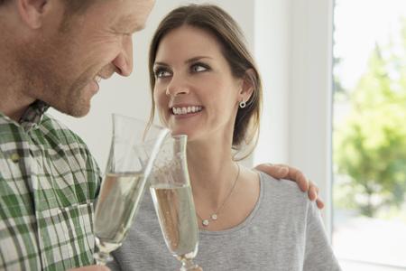 Couple celebrating drinking toasting new home