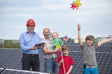 wind powered building: Man ipad father kids solar park LANG_EVOIMAGES