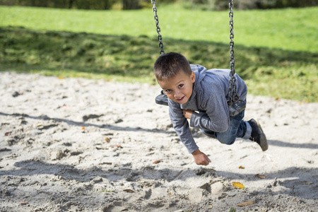 luft: Young small boy swinging playground swing