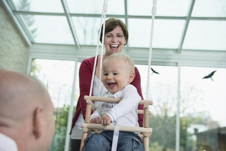 ardor: Happy toddler sitting in a swing