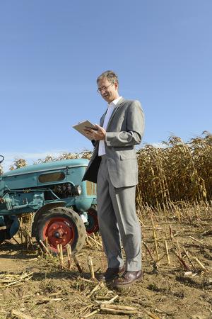 Hombre de negocios con tableta digital en campo de maíz