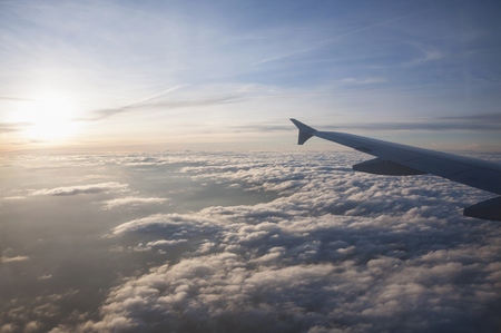 outdoor lighting: Aerial view of airplane flying over clouds at sunset