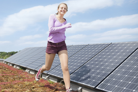 Young teenage girl jogging solar park