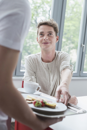 Young man offering plate with breakfast to another man, smiling