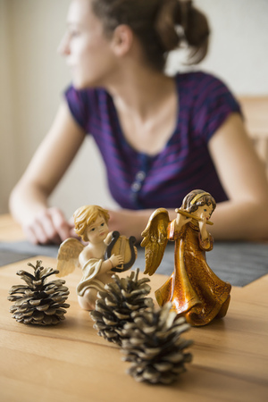 animal figurines: Decorative Christmas angel figurines with musical instruments and pine cones in front of teenage girl, Bavaria, Germany