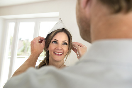 Man helping wife hat paper decorating smiling
