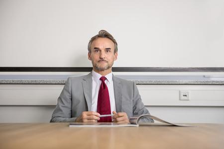 Portrait businessman suit table office manager LANG_EVOIMAGES