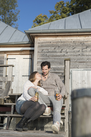 near beer: Young couple sitting boathouse jetty drinking beer