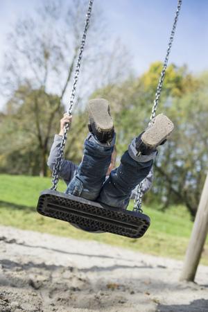 luft: Boy playing swinging playground swing sand