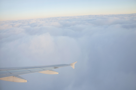 lighted: Aerial view of airplane flying over clouds at sunset