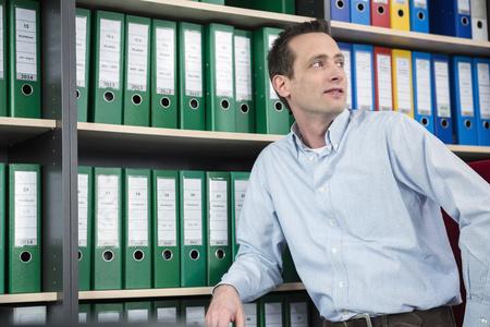 Portrait man office filing cabinet thinking